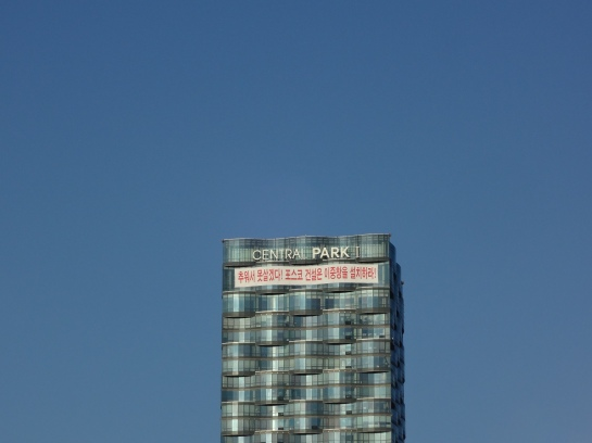 Songdo's Central Park building, with a protest sign outside
