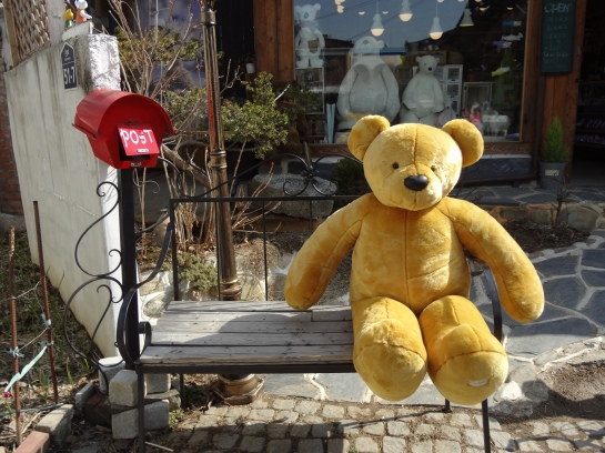 A teddy bear on a bench. Of course.